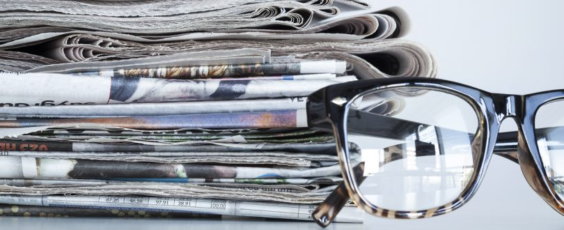 Reading glasses in front of a stack of newspapers